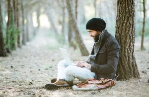 Man stiing under tree and working on laptop